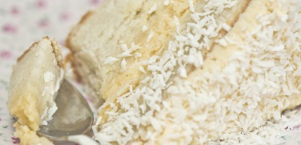 a slice of old fashioned coconut cake with coconut frosting